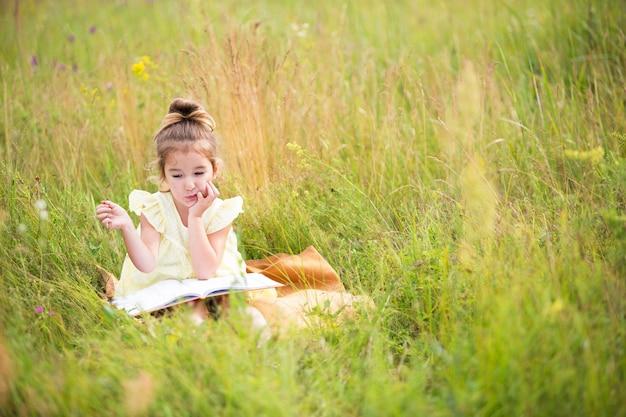 Meisje in een gele jurk zit in het gras op een deken in een veld en leest een papieren boek. internationale kinderdag. zomertijd, kindertijd, onderwijs en amusement, cottage-kern. ruimte kopiëren