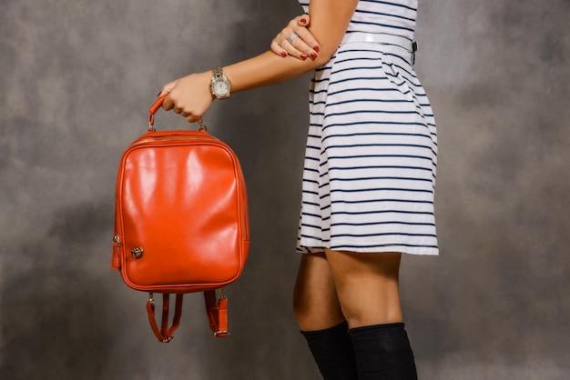 Meisje in een gestreepte jurk met een rode zak op grijs
