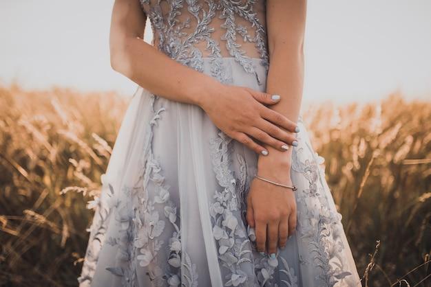 Meisje in een grijze jurk met bloemen toont haar prachtige blauwe manicure op een achtergrond van hoog geel gras bij zonsondergang.