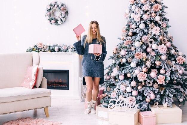 Meisje in een grijze trui opende de geschenkdoos in een gezellige kamer met een open haard, een bank en een kerstboom.