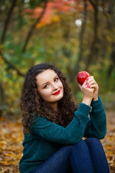 Meisje in een groene trui en een appel in haar handen in het herfstbos