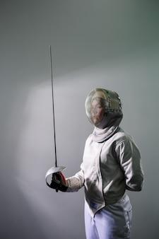 Meisje in een hekwerk kostuum met een zwaard in de hand geïsoleerd op een witte studio achtergrond. jonge meisjes oefenen en oefenen. sport, gezonde levensstijl.