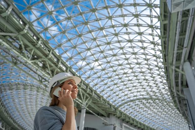 Meisje in een helm die op telefoon het nemen spreekt