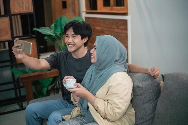 Meisje in een hijab en een aziatische man voeren videogesprekken met behulp van een slimme telefoon in de woonkamer terwijl ze een kopje vasthoudt terwijl ze op een bank zit