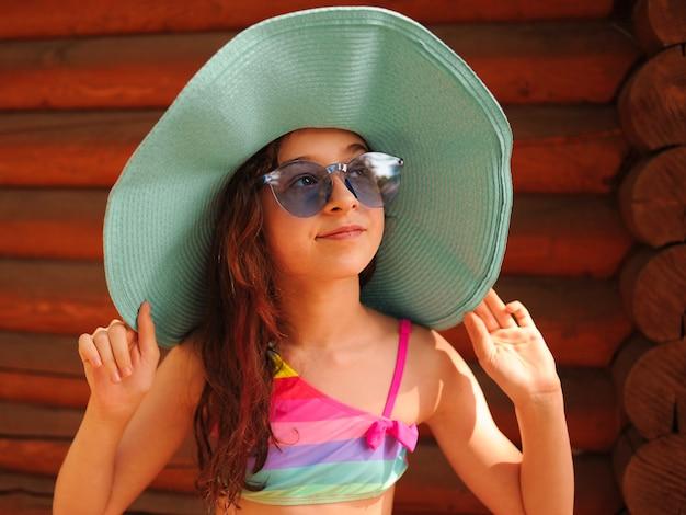 Meisje in een hoed en bril in de zomer. portret van een mooi meisje met een bril.