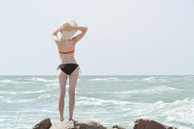 Meisje in een hoed en een zwempak aan zee. achteraanzicht