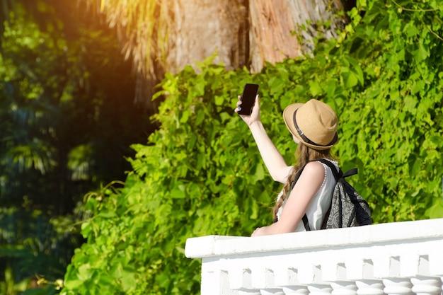 Meisje in een hoed en met een rugzak maakt selfie in het park