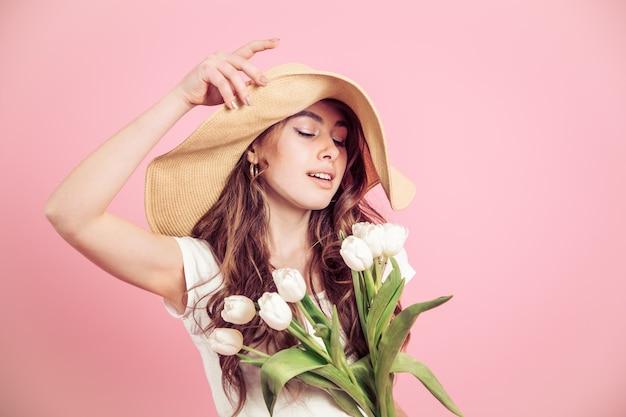Meisje in een hoed en tulpen op een gekleurde achtergrond