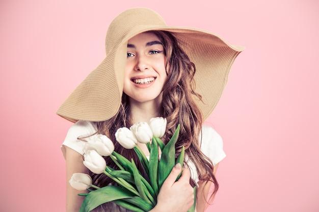 Meisje in een hoed en tulpen op een gekleurde muur