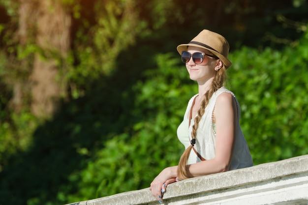 Meisje in een hoed en zonnebril die van aard genieten. zonnige dag, park