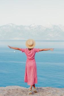 Meisje in een hoed in de buurt van de zee aan de rand van een klif met de zee en de bergen op de achtergrond