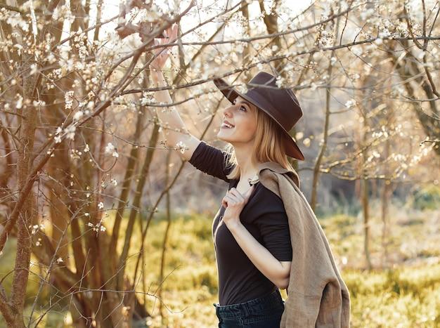Meisje in een hoed in een tuin van de kersenbloesem bij zonsondergang