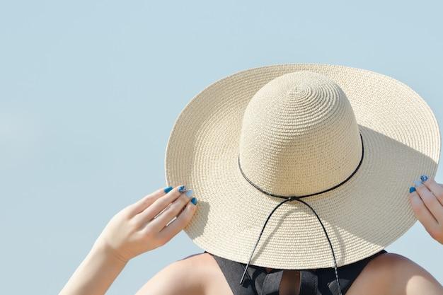 Meisje in een hoed kijkt naar de hemel.