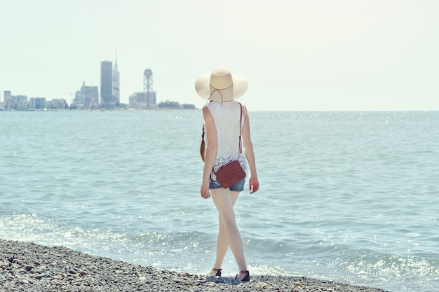 Meisje in een hoed loopt langs de kust. stad in de verte. uitzicht vanaf de achterkant