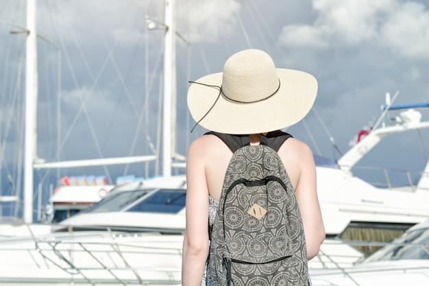 Meisje in een hoed met een rugzak dichtbij schip. achteraanzicht