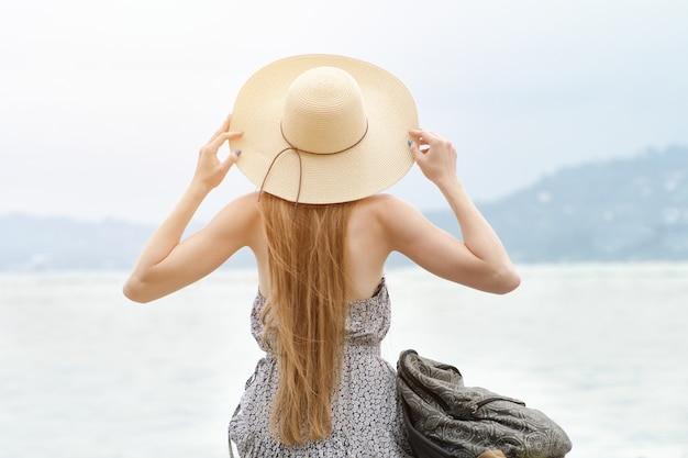Meisje in een hoed met een rugzak zittend op de pier. bergen op de achtergrond. uitzicht vanaf de achterkant