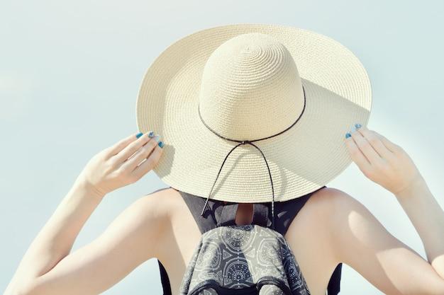 Meisje in een hoed op een achtergrond van heldere hemel