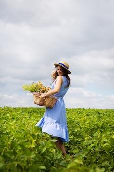 Meisje in een hoed staat op een groen veld met een mand met bloemen
