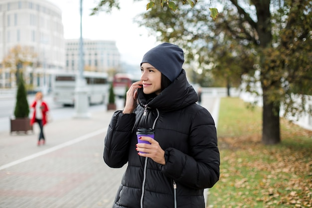 Meisje in een jas en een hoed op straat, met een glas en een telefoon. hoge kwaliteit foto