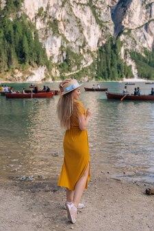 Meisje in een jurk en schipper aan de oever van een bergmeer met houten boten. dolomieten, italië.