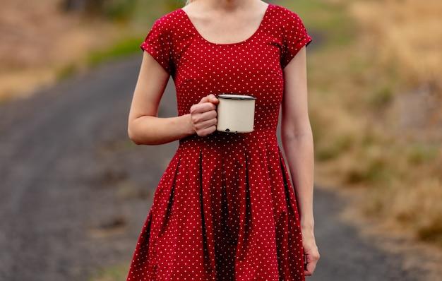 Meisje in een jurk in polka dot met kop op landelijke weg