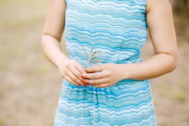 Meisje in een jurk met een zeegolfornament heeft een groen takje van een olijfboom in haar handen