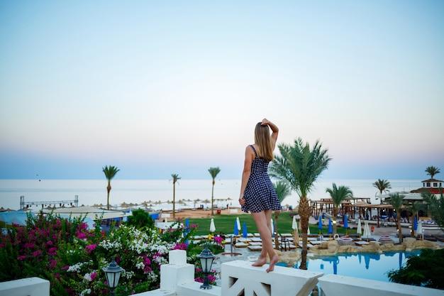 Meisje in een jurk op een achtergrond van zonsondergang en zee