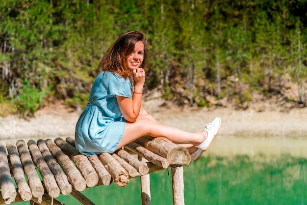Meisje in een jurk op een brug boven een bergmeer met helder water en uitzicht op een groen bos