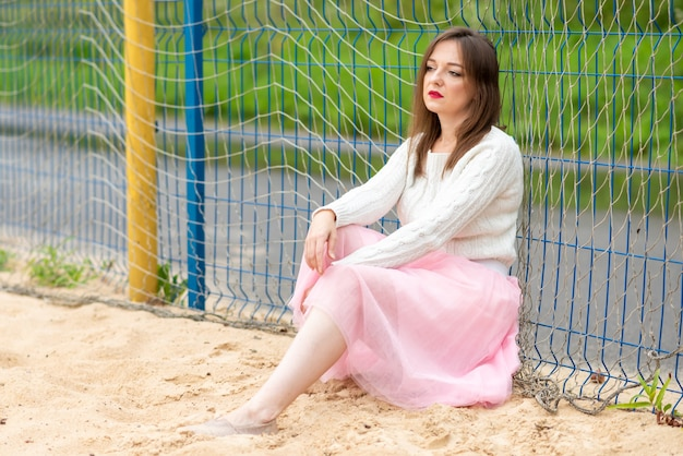 Meisje in een jurk op het veld voor strandvoetbal. hoge kwaliteit foto