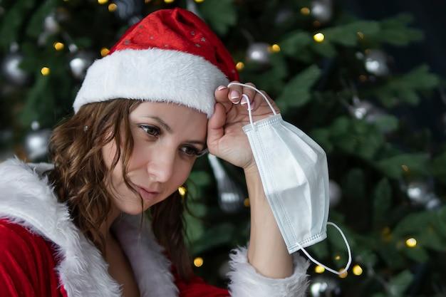 Meisje in een kerstmankostuum deed een beschermend medisch masker af tegen de achtergrond van een kerstboom. concept voor het einde van het coronavirus en 2020. mevrouw de kerstman ziek covid 19