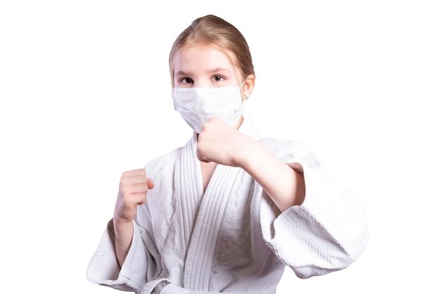 Meisje in een kimonojudo. getraind in een masker. geïsoleerd op een witte achtergrond. hoge kwaliteit foto
