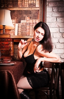 Meisje in een korset voor een restauranttafel
