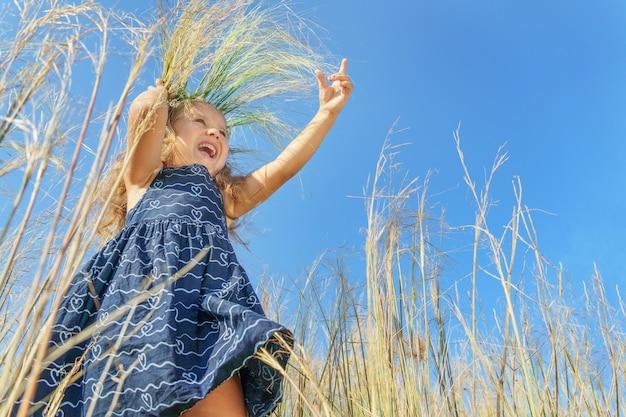Meisje in een krans op een achtergrond van blauwe lucht. gelukkig kind, gelukkige jeugd.