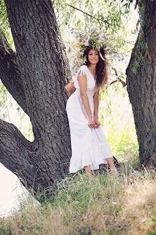 Meisje in een krans van de veldbloemen bij de boom