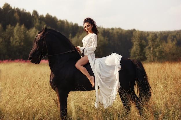 Meisje in een lange jurk berijden van een paard