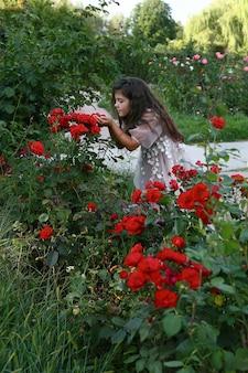 Meisje in een lange jurk in rozentuin