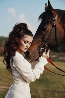 Meisje in een lange jurk staat in de buurt van paard, mooie vrouw streelt een paard en houdt hoofdstel in veld in de herfst. landleven en mode