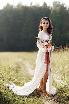Meisje in een lange jurk staat in een veld met krans op haar hoofd en een boeket bloemen in haar handen