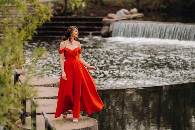 Meisje in een lange rode jurk in de buurt van het meer in het park bij zonsondergang.