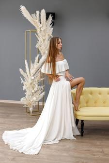 Meisje in een lange witte jurk bij de bank op een grijze achtergrond