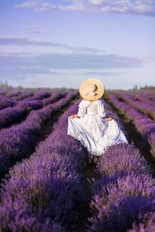 Meisje in een lange witte jurk loopt in een lavendelveld. uitzicht vanaf de achterkant. ze draagt een grote strohoed.