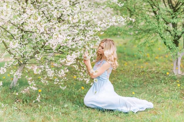 Meisje in een lentetuin die bloemen bewonderen