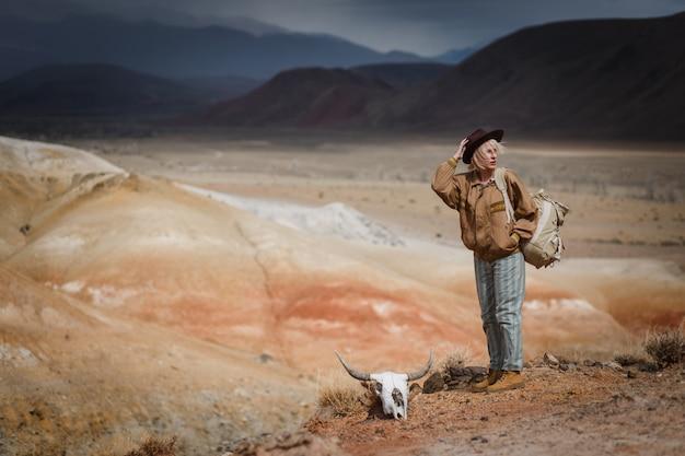 Meisje in een leren jas wandelen in de woestijn