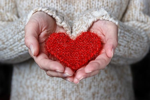 Meisje in een lichte trui geeft een gebreid hart.