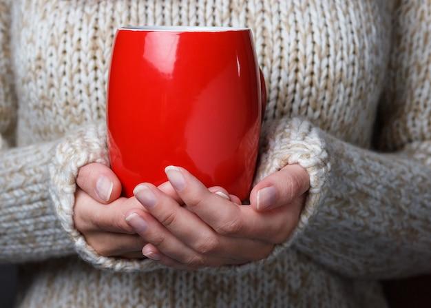 Meisje in een lichte warme trui met een rode kop koffie