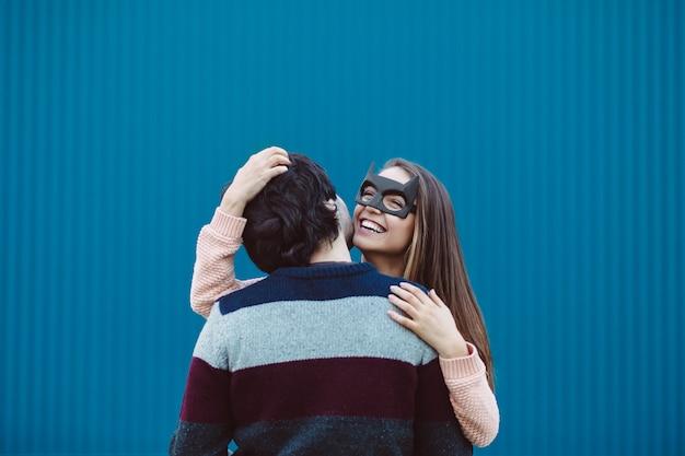 Meisje in een masker dat haar jonge kerel kust.