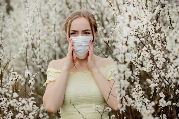 Meisje in een medisch masker. meisje in het voorjaar onder de bloeiende tuin. een meisje in een beschermend medisch masker. lente allergie concept
