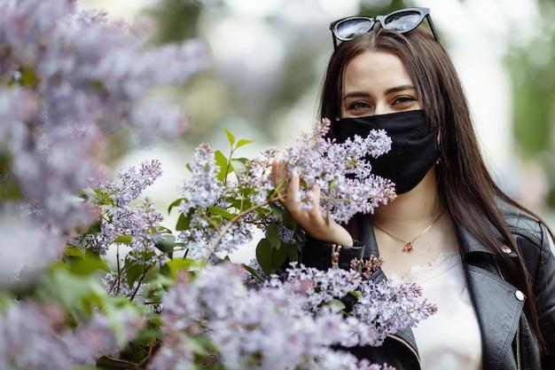 Meisje in een medisch masker met bloeiende sering in het park. zwarte masker. coronavirus bescherming. lente allergie