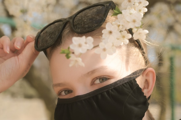 Meisje in een medisch masker op een achtergrond van bloeiende kersen.
