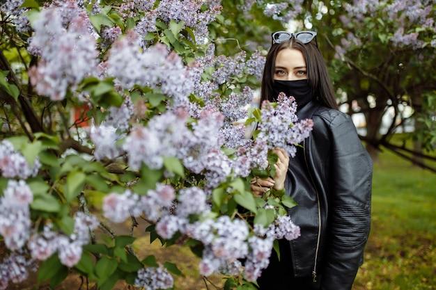 Meisje in een medisch masker op een achtergrond van bloeiende seringen. zwarte masker. bescherming tegen virus, griep. coronavirus bescherming. epidemie van coronavirus